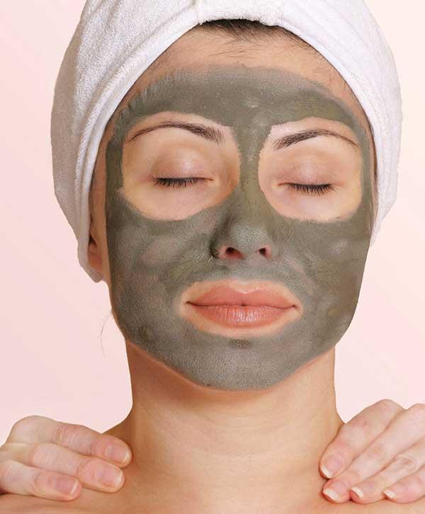Chica con mascarilla facial para el acné