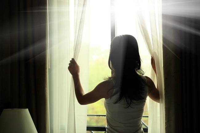 chica en la ventana viendo el sol